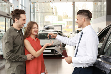 Young couple buying car in salon