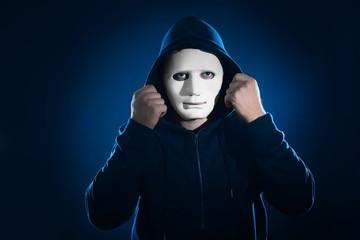 Hacker in mask on dark background