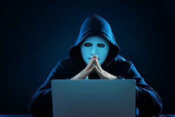 Hacker in mask using laptop in dark room
