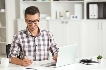 Attractive man with laptop and smartphone in office