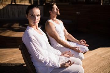 Couple performing yoga at safari vacation