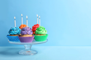 Tasty cupcakes with candles on color background