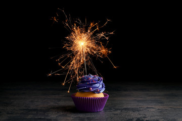 Tasty cupcake on table against black background