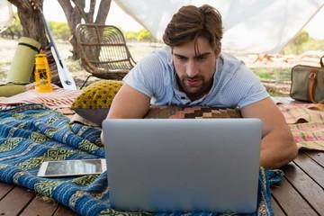 Man using laptop in tent