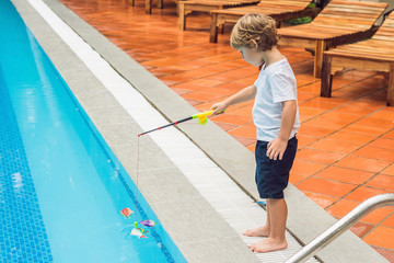 A little cute boy is catching a toy fish in the pool