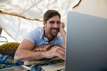 Happy man using laptop in tent