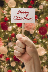 Hand Holding Merry Christmas Card In Front of Decorated Christmas Tree.