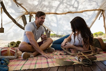 Happy couple playing cards in tent