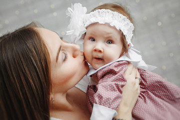 Portrait of happy young woman with cute baby on light background