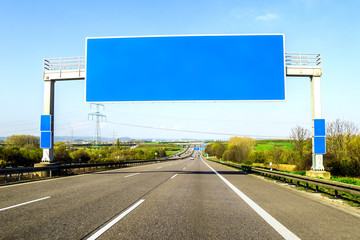 Blank blue freeway sign over the road on sunny day