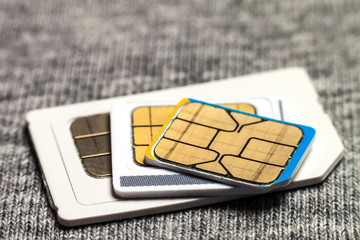Set of mini, micro and nano simcard. Isolated on grey cloth texture background