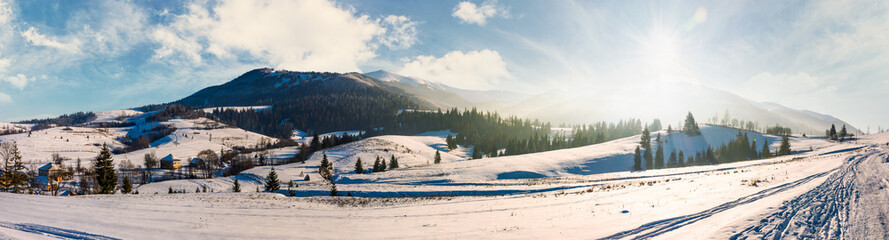forested valley of Pylypets village in Carpathians. Gorgeous winter landscape with Borzhava mountain ridge on winter sunny day