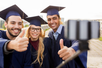 students or graduates taking selfie by smartphone