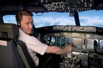 Portrait of handsome young male pilot flying airplane
