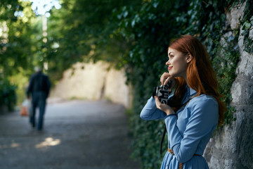 Young beautiful woman is walking outdoors with a camera