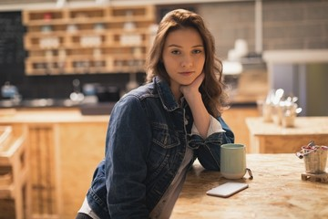 Woman sitting in café with coffee on table