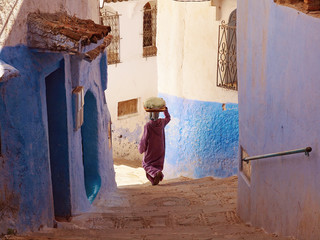 Photo sur Plexiglas Maroc A woman caring the bread on her head and walking down the blue-white streets in Chefchaouen - the blue city Morocco - amazing palette of blue and white buildings