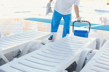 worker at the hotel removes the water from the deck chairs after the rain