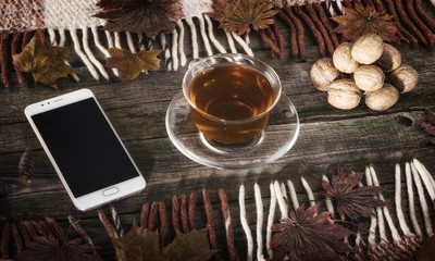 A cup of tea and a mobile phone on a vintage wood background.