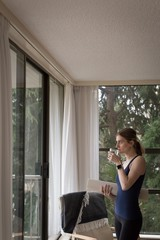 Side view of woman drinking water while standing by window