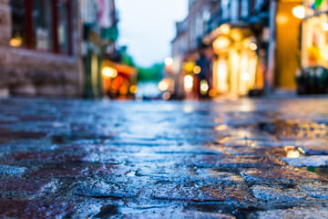 Macro closeup of colorful, vibrant and cobblestone street at night after rain with reflection of...