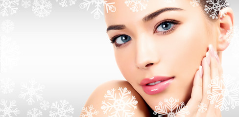 Closeup headshot portrait of a beautiful woman with beauty face and clean smooth soft skin , mild makeup. Grey steel background with snowflakes and a place for your information