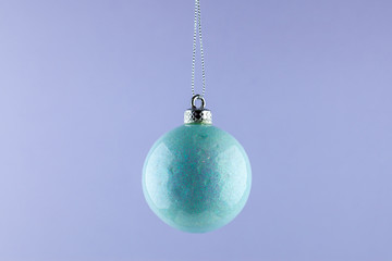 Blue christmas ball ornament on violet background. minimal concept idea