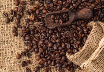 Wooden scoop put on background of coffee beans.