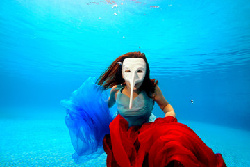Girl underwater in a white mask posing on the blue background. Portrait. Horizontal orientation. Shooting under water