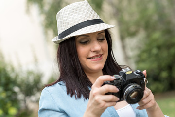 Portrait of pretty young woman using a camera