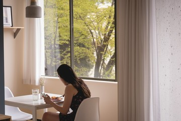 Side view of woman using phone while having breakfast at home