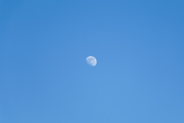 The shape of the moon on a blue sky day