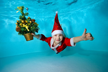 A little boy in a cap Santa Claus swimming underwater with outstretched arms, and with a Christmas tree in hand on blue background, looking at camera and smiling. Shooting under water