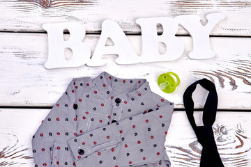 Baby boy modern boutique clothes. Toddler boy cute grey dotted shirt, black tie, pacifier, word baby, white wooden background.