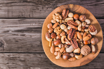 Plate of various fresh nuts on old rustic table top view with copy space