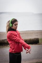 Woman exercising while listening to music at beach side