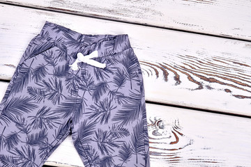 Kids patterned casual trousers. Toddler boy spring or autumn fashion pants, old wooden background. Kids fashion outfit.