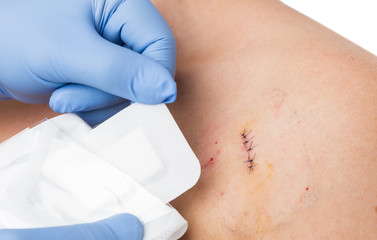 Doctor hands patching stitched surgery with new sterile bandage