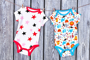 Infants clean apparel hanging on rope. Newborn kids printed bodysuits drying on clothesline on old wooden background.