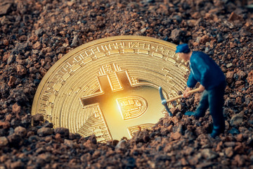 macro miner figurine digging ground to uncover big shiny bitcoin