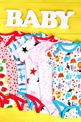 Newborn kids cute organic garment. Infants high quality patterned rompers on colored wooden background, top view.