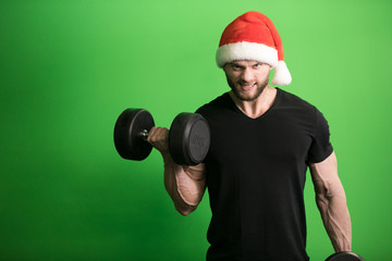 Man in Santa hat pumping bicep on green background