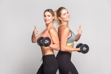 Cute blonde girlfriends standing back to back and holding dumbbell