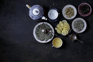 Different Tea Leaves with slices of lemon on a dark background