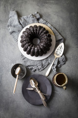Dark chocolate bundt cake, spoons and decorative spatula