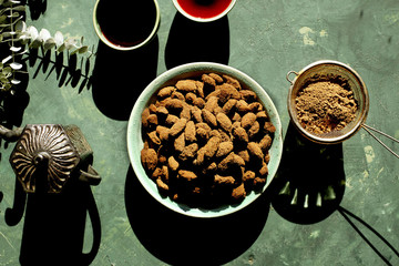Cacao Ashwagandha Almonds served with hibiscus tea. Photographed on a green background.