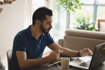 Man using laptop while having breakfast