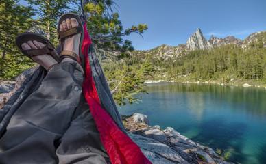 Hiker Lounges in Hammock over Alpine Lake