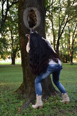 a girl with long black hair taking pictures of a tree in the park