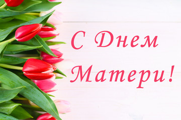 Pink tulips on a white wooden table with an inscription in Russian - Happy Mother's Day.
